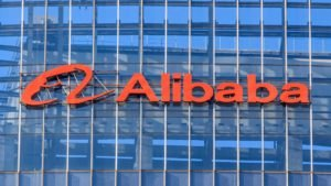 Alibaba (BABA) logo on the side of a glass-walled building.